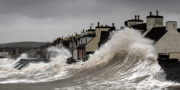 Climate change can lead to stronger winds, rising seas and flooding. Here huge waves crashing over the front at Port William, Great Britain 2014. Photo: David Baird (CC BY-SA 2.0)